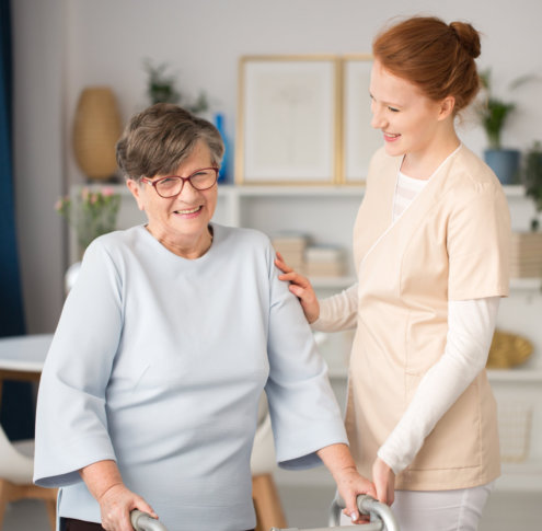a caregiver assisting a senior woman stand