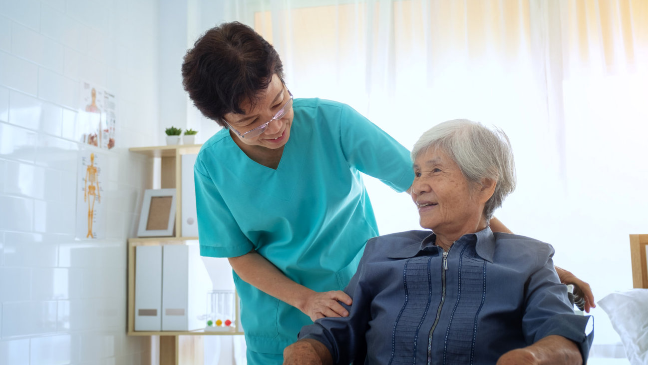 a caregiver smiling at her senior patient