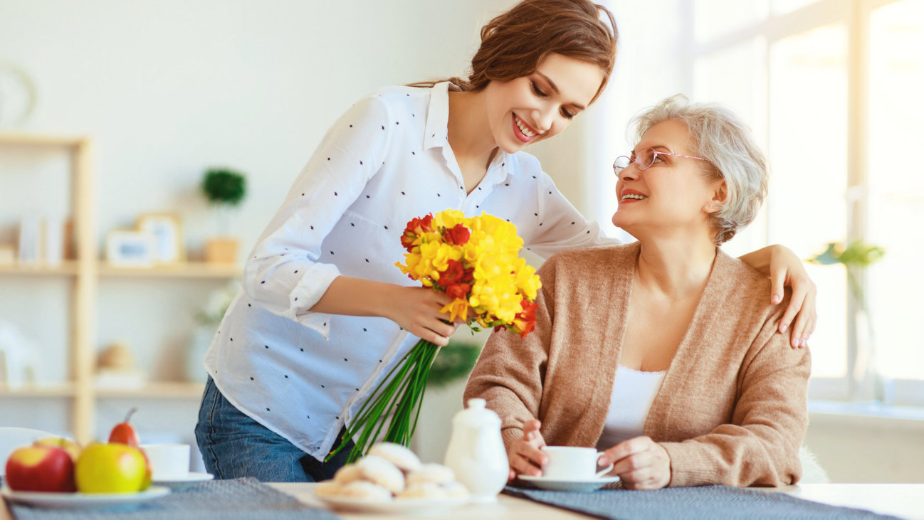 a caregiver giving flowers to the senior woman