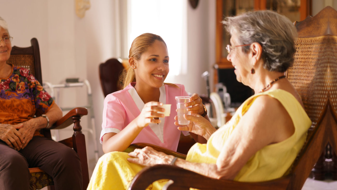 a caregiver giving medicine and water to a senior woman